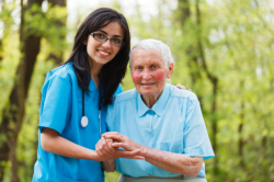 caregiver assisting old woman to walk