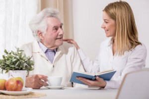 caregiver assisting old man to read the book